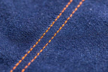 stitches: Blue jeans denim texture with orange stitches