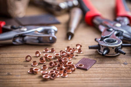 hole punch: Leather hole punch and rivets on wooden background
