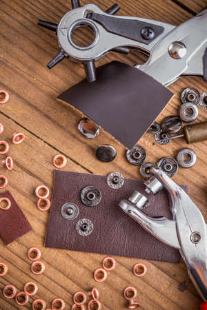 puncture: Leather crafting DIY tools on wooden table Stock Photo