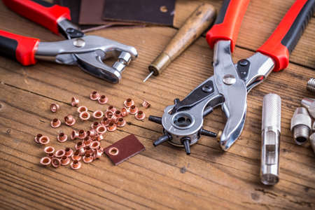 eyelet: Leather punch tools with brass rings on wooden board Stock Photo