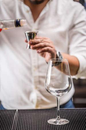 barmen: Bartender pouring liqueur into a jigger to prepare a cocktail