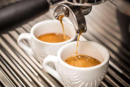 Machine à expresso versant du café dans des tasses blanches Banque d'images