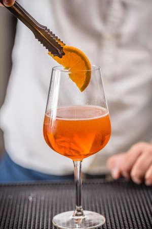 decorating: Barman decorating cocktail with lemon