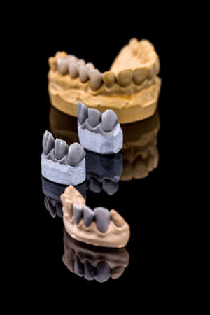 prothesis: Artificial teeth, wax models on reflection black background