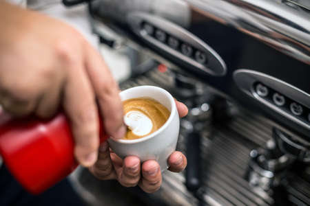 froth: Barista preparing proper cappuccino pouring milk froth in a cup Stock Photo