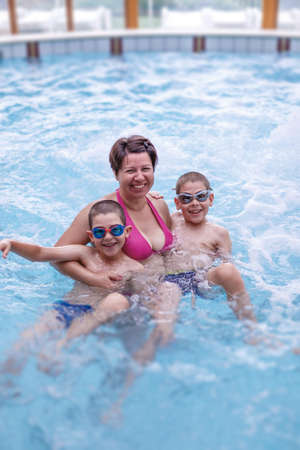 motherly: Boys enjoying with his mother in the pool