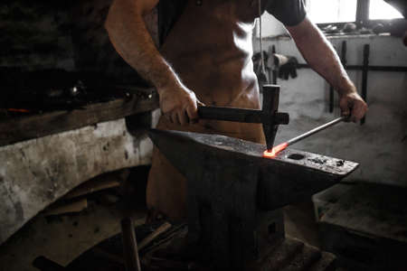 farriery: The hands of a blacksmith at work in the smithy Stock Photo