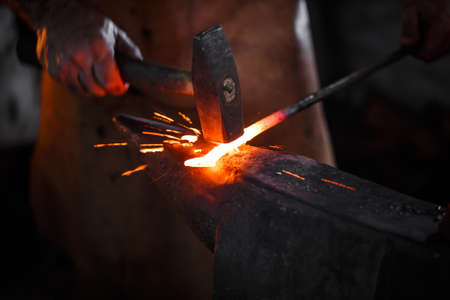 The blacksmith manually forging the molten metal on the anvil in smithy with spark fireworks Stockfoto