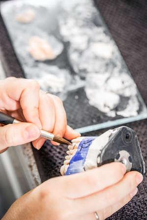 Closeup of dental technician applying ceramics to teeth before put into furnace