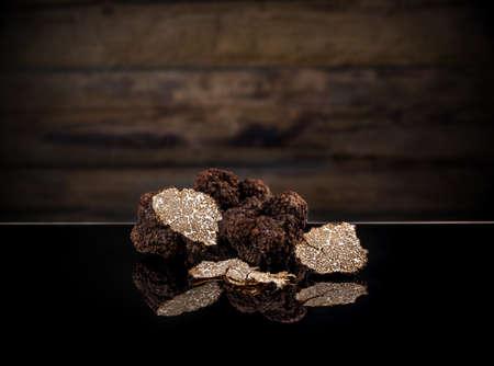 Black autumn truffles on dark clipping path background Standard-Bild