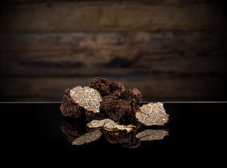 Black autumn truffles on dark clipping path background Banque d'images