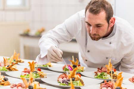 Maschio chef guarnendo il suo piatto antipasto, pronto a servire