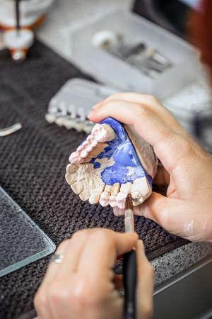 Dental technician applying ceramics to teeth before put into furnace