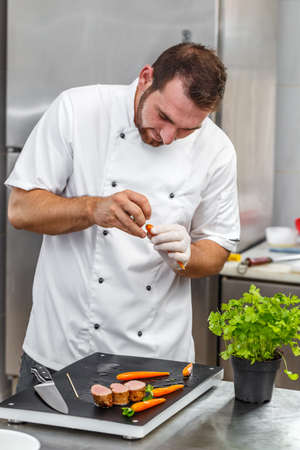 decorating: Chef decorating carrots with parsley Stock Photo