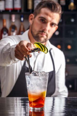 barman: Barman decorating cocktail with lime Stock Photo