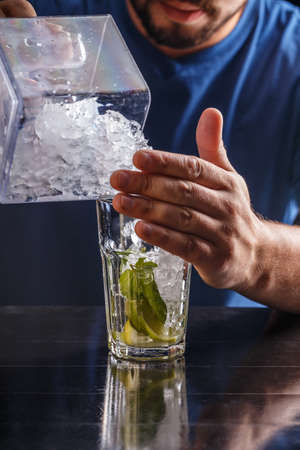 putting: Bartender putting broken ice in a glass