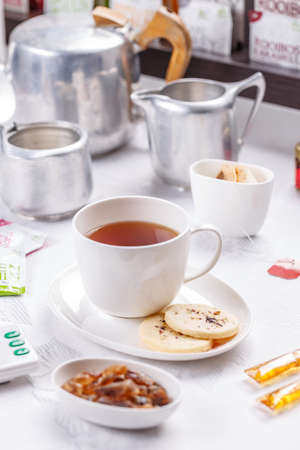 oclock: White ceramic cup and saucer with tea and shortbread biscuit