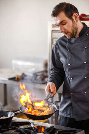 Chef is stirring vegetables in frying pan