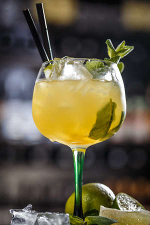 Cocktail is consisting of tequila, freshly squeezed lime juice, mango juice and garnished with a lime slice and mint leaf