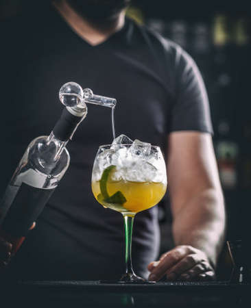 adding: Barman at work, he is preparing cocktails, concept about service and beverages Stock Photo