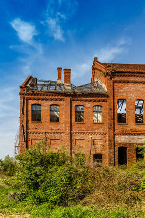 Abandoned brick building with broken windows, weed grown