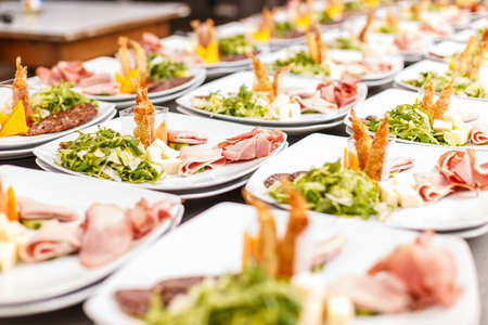 Lot of appetizer plates with salami, shrimp and lettuce