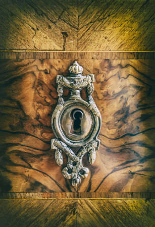 Antiek metaalsleutelgat in oude houten garderobe, close-up