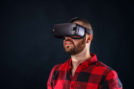 Young bearded man wearing virtual reality glasses photo