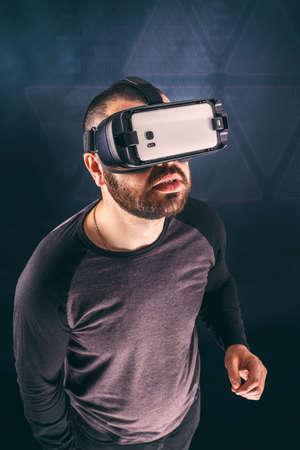 Man wearing virtual reality device, studio shot photo