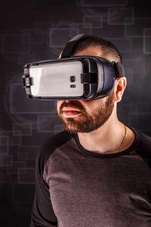Man wearing virtual reality goggles, studio shot photo