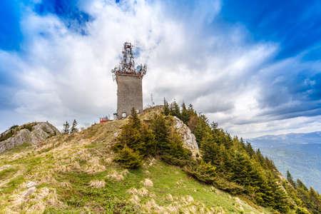Telecommunication tower with satellite dishes and radio antennas on Postavaru peak, Poiana Brasov, Romania.