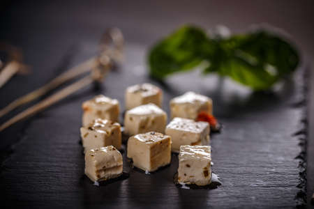Cubes of cheese, seasoned with herbs, close up