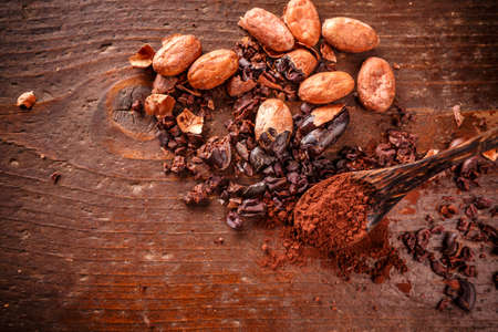 nib: Composition of cacao nibs, cacao beans and cacao powder on old wooden background Stock Photo