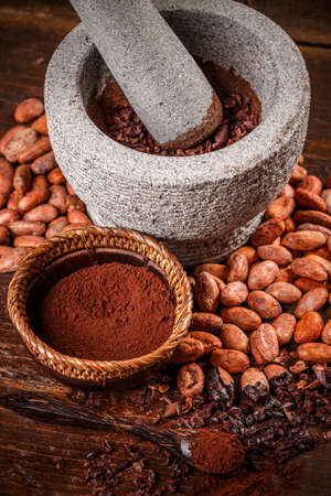 Cocoa production with stone mortar and pestle with raw, peeled, and crushed cacao beans