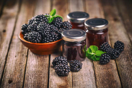 Tasty blackberry jam and fresh berries, on rustic wooden background Stock Photo