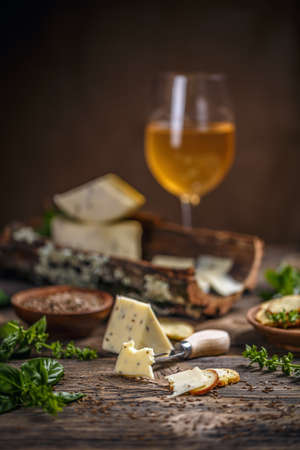 Cheese with caraway seeds on old wooden background