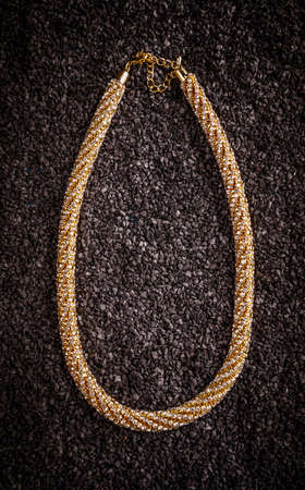 Goldplated necklace with small glass stones on black background