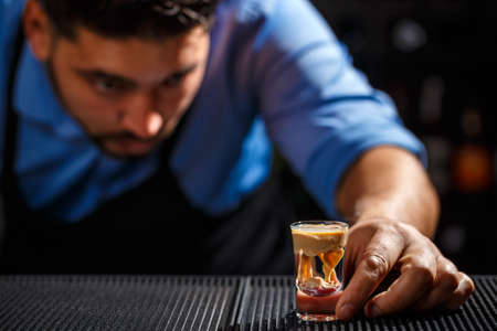 The bartender looks his creation, he makes Brain shot Stock Photo