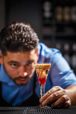 The bartender looks his creation, he makes Bloody Brain shot