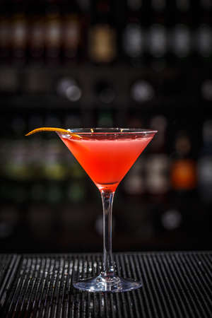 Closeup glass of cosmopolitan cocktail decorated with orange peel at bar background Stock Photo