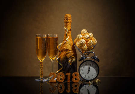 2018 New Years Eve celebration background with pair of flutes, bottle of champagne and a clock