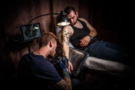 Professional tattoo artist makes a tattoo Stock Photo