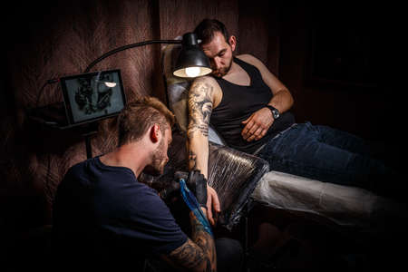 Professional tattoo artist makes a tattoo Archivio Fotografico