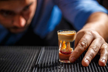 The bartender looks his creation, he makes Brain shot Stock Photo