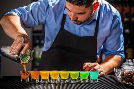 Dozijn van kleurrijke regenboogcocktails die op de teller door een barman worden voorbereid