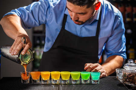 Dozen of colorful rainbow cocktails being prepared on the counter by a bartender