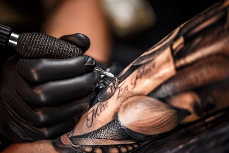 A professional tattoo artist introduces black ink into the skin using a needle from a tattoo machine.