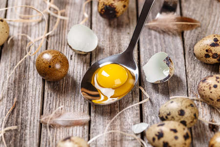 Fresh raw quail eggs in spoon on wooden background Stock Photo