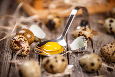 Raw quail eggs in spoon on a rustic wooden table
