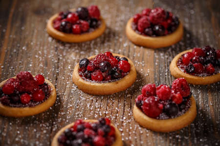 Berry tartlets dessert, pastry cakes sweets with fresh berries